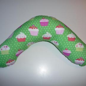 """Varetype: """"Boomerang-pude"""" til baby Størrelse: One Size Farve: diverse  Fin lille """"boomerangpude"""", som hjælper baby med at træne nakken...og hindrer at han/hun slår hagen, når hovedet pludselig bliver for tungt;)  Med fiberfyld. Kan maskinvaskes ved 40 grader. Stoffet er vasket i Neutral inden opsyning.  Kan syes i et væld af farver...se billederne  God barselsgave:)  Se også mine andre annoncer med bl.a barnevognspuder, nuldreklude, suttekæder, hynde til højstol mm;)"""