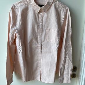Lys rosa skjorte i tætsiddende model. 100 % bomuld.
