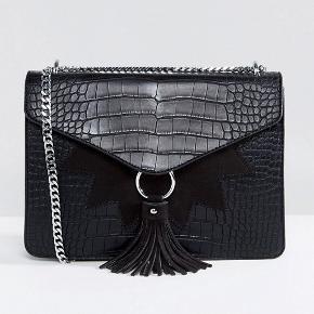 Smuk taske i imiteret slangeskind fra Skinnydip. Aldrig brugt, i perfekt stand. Kan sendes hvis køber betaler for fragt.