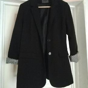 Str 40 Klassisk sort blazer med sort/hvid stribet lining i ærmerne.  Kan maskinvaskes på 30°  I rigtig fin stand  Prisen er fast, fordi den er fair 😉