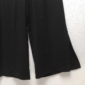 Lette bukser med slids ved læggen. De lynes i siden og er uden lommer bagtil. Aldrig brugt.
