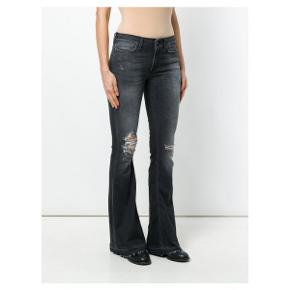 Dunlop jeans str. 28. Aldrig brugt. Flot gråblå farve. stretch, rå kanter forneden. Porto 38 kr. Nypris 2000.- Kan ses i Rungsted