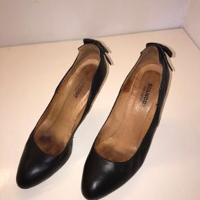 Sorte heels / stilletter i læder str.38. Gode men brugte- slid ses på hæle som trænger til nye tipper og indvendigt. Fin detalje med sløjfe siddende bagpå.  Nypris var vist nok 599kr Kan ikke passe dem mere, hvorfor de sælges.