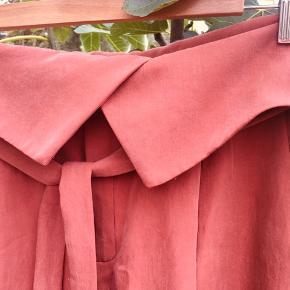 Lækre bukser i silkeagtig kvalitet. Str L, men fitter sagtens en str M. Der er en mindre plet ved folden øverst (se billede 3), men den er ikke særlig tydelig.