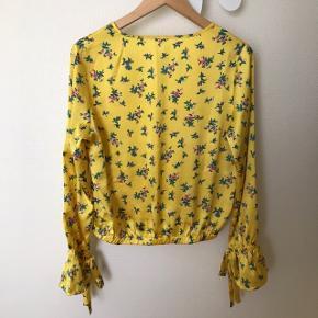 """Super flot bluse i """"silke look"""" fra NLY TREND.  Blusen har sløjfer i ærmerne, som giver den et eksklusivt look. Aldrig brugt. Sender gerne."""