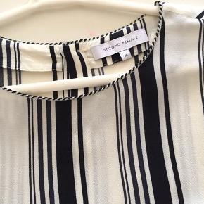Bluse i 100% blød viskose. Stribet sort/ råhvid.  Knapper i ryggen og ved håndleddet. Spørg evt. efter billeder med den på.