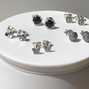 5 par ørestikkere fra PANDORA i sterlingsølv. Sælges kun samlet. 2 forskellige med blomster 1 med sommerfugl 1 med mørkeblå faceteret krystal. 1 par runde droplet m. sten.