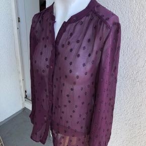 Smuk skjorte med fine dekorationer. Materialet er 100% silke. Mål er: Brystmål: ca. 2*50 cm Længde: ca. 64 cm Den er kun brugt én gang og er som ny :-) Min. pris 150 plus porto