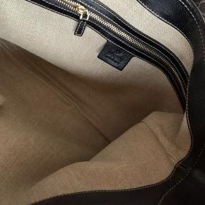 Vintage skuldertaske fra Gucci sælges i flot stand. Købt i Gucci's butik i London. Original kvittering og dustbag medfølger. Tasken har kun haft mig som ejer.  Kommer fra et ikke-ryger hjem.  Handler via Mobilepay - sendes med GLS track/trace uden omdeling (53kr).  Ved ts-handel betaler køber ts-gebyret.