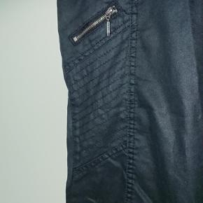 Smarte sorte bukser fra Jensen, i str 44. Lynlås detaljer og nitter. Livvidde: ca 50x 2 cm, og indvendig benlængde ca 64 cm. Lukkes foran med 2 knapper og lynlås.