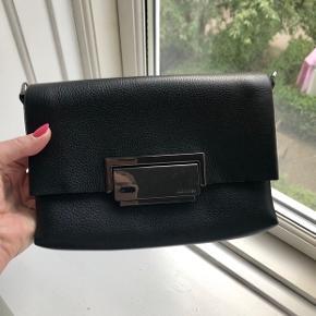 Smuk sort clucth fra Calvin Klein i lædder udvendig og ruskind indvendigt. Fin lille rem til over skulderen.  Nypris: 1.499kr.