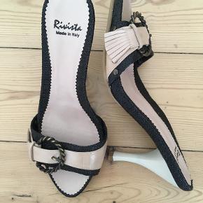 Flotte sandaler i lys beige og sort med hæl fra Rivista. Indvendig længde: ca.25cm. Hælhøjden er ca. 9 cm. (målt bagpå hælen).  Sandalerne har aldrig været brugt.  Pris 350kr. pp.