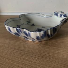 Fin porcelænsskål fra B&G, formet som en muslingskal. Fremstår i perfekt stand og uden skår. 1. sort. Mål; Højde 4 cm og længde x bredde 17x17 cm