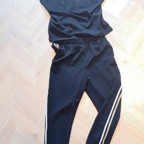Neo noir buksedragt, men guld stribe på ben og ærmer. Er prøvet på, men aldrig brugt. Str. Small
