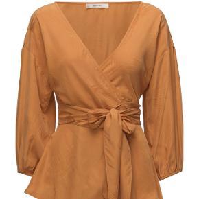 Super fin slå-om-bluse i flot orange. Brugt to gange. Nypris 1300 kr. Materiale: 58% cupro, 42% lyocell.