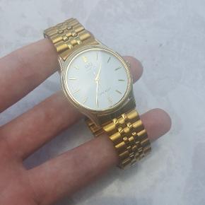 Super fint ur med guld rem. Smart elastik rem det sidder behageligt unden at skulle skifte link.  Diameter er 3,5 cm og uret kan passe et håndled ned til  21 cm i omkreds. Uret har sat nyt batteri i samt ridsefrit glas. Quatz