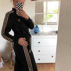 Sort Adidas tracksuit sæt med guld striber. Byd gerne