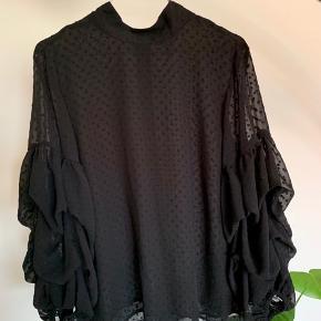 Sød bluse fra H&M brugt få gange, fine knapper ned langs ryggen og elastik ved ærmerne. Størrelse 36, men kan også passes af en 38.