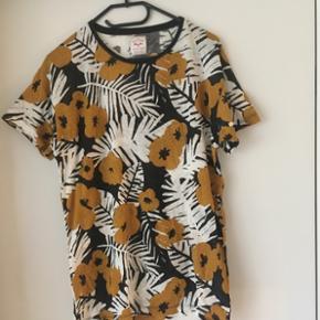 Flot blomstret t-shirt fra Zara str.M sælges. Den har aldrig været brugt.Perfekt til sommer, da den er fremstillet af 78% bomuld og 22% af hør. Porto DAO 38 kr.