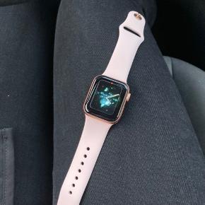 Apple Watch 4 sælges.  Urskiven er 40 mm. og i guldfarvet aluminium med lyserøde remme. Den har cellular, så man kan benytte e-simkort og ikke er afhængig af Wifi. Brugt få gange og har absolut ingen ridser eller skader. Original kasse, kvittering og oplader følger med. Købt for få måneder siden hos 3.  FAST PRIS: 2800 kr. + evt. porto og handelsgebyrer  Befinder sig i Esbjerg, hvor den kan ses og afhentes.