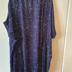 Adia kjole/tunika i størrelse M = 46-48 I 100% let viskose i kimonofacon med ærmer til albue, V-udskæring og gennemknappet. Små, hvide nister/prikker af forskellig størrelse strøet tilfældigt ud på mørkeblå baggrund. Masser af vidde, der falder helt blødt om kroppen, da stoffet er meget fint og let. Måler over brystet 180 cm, og længden er 102 cm. Jeg har lagt billeder op, hvor jeg har tapet kjolen op på mit skab, så man kan se kimonofaconen. Brugt, men i god stand. BYTTER IKKE!