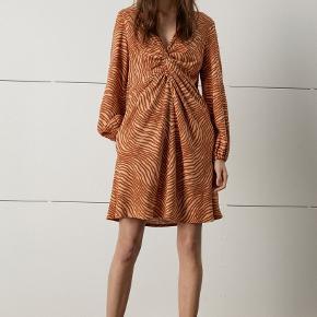 Denne kjole har en cool, klassisk silhuet med knude i fronten, som giver kjolen et interessant look. Kjolen er simpelthen et musthave i din garderobe. Håndleddene er elastiske og giver dermed en flot drapering i ærmet. Materiale: 20% hør, 80% viskose. Nypris: 2500kr.