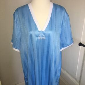 Lyseblå/turkis T-shirt kjole fra ellesse. Størrelse uk 14, v hals og hvide detaljer. Ved køb af flere ting kan der opnås mængderabat