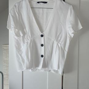 Fin hvid t-shirt med v-udskæring og knapper. Den er brugt to gange i få timer og fremstår derfor som ny. Perfekt til de kommende varme dage ☀️