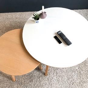Iris sofaborde fra Ilva. Det store bord har hvid laminat bordplade og hvidolieret ben i eg. Det måler 45x90cm. Det lille bord er fremstillet i egefiner med ben i hvidolieret eg. Det måler 42,5 x 60cm. Bordene er ca. fem år gamle men står i rigtig fin stand dog med en enkelt bemærkning, det lille bord har nogle små hvide mærker på kanten af bordpladen (se billeder). Afhentes i Herning.