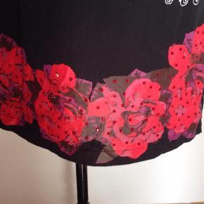 Varetype: Mini Størrelse: 44 Farve: Sort Oprindelig købspris: 1000 kr. Prisen angivet er inklusiv forsendelse.  Super flot Desigual kort kjole. Sort med bort med store røde/lilla blomster med røde perler. Længde 82 cm. Brystmål: 50 cm.