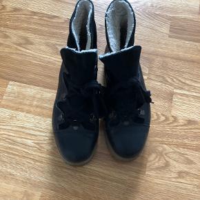 Lækre vinterstøvler fra Ganni i modellen Mascha Texas Black.   Støvlen er med for og praktisk med gummisål til vinter.