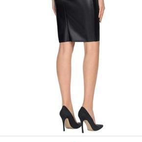 Imiteret sort lædernederdel med stretch. Sidder tæt og flot. Kun brugt få gange. Klassisk nederdel.  Nypris er 1500 kr.