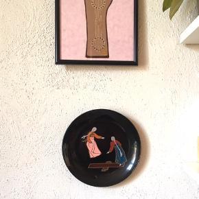 Tallerken til ophæng. vintage. Den er i sort plast og dekorationen er emalje. 22cm i dia.