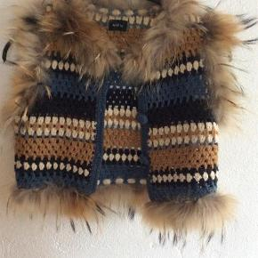 Varetype: Vest Farve: Brunlig  Sød og sjov vest af 80% uld og med pels af vaskebjørn.... Farverne er brune - blå med indvævet guldtråd. Nypris 2500