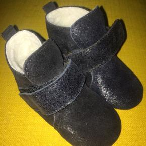 Da min søn desværre har for tykke fødder til dem, sælger jeg disse lækre sorte glitter skind sutsko med uld for og skridsikker gummisål. De passer bedst til smalle fødder!  - Jeg har kassen som følger med.  - I må gerne komme og prøve.  - Prisen er eksklusiv porto. Ny pris: 300 kr.