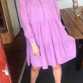 Smuk rosa kjole fra Samsøe i en løs model med sølv lurex tråde, knaplukning ned foran foroven, samt underkjole. 💜🥂  str M: Farver: Lavendel Kvalitet: 100% Polyester Vaskeanvisninger: Maskinvask 30 grader