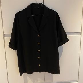 Kortærmet sort skjorte med træ knap detaljer.  Brugt 2-4 gange.