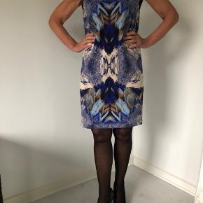 Smuk kjole fra YAS str. 34 med abstrakt mønster i blå nuancer samt brun, lys beige og sort.  Uden ærmer. Der er en smart elastik-detalje øverst på ryggen.  Der er en blød, sort underkjole.  Længde fra skulder er 88 cm, og både brystmål og taljemål er 98 cm.  Fremstillet af 95% polyester og 55 spandex (underkjolen er 100% polyester).  Bærer ikke præg af brug.