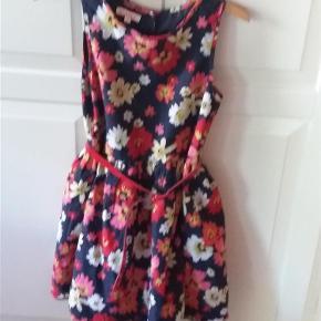 Elegant kjole med blomster og lavmælte. Lukkes med knappet i ryggen.  Lidt lille i størrelsen - min pige har brugt den da hun var 7-8 år.  Se også mine andre annoncer.  Kjole Farve: Blå