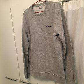 Jeg sælger denne lækre Champion sweatshirt i grå.  Stand: 8/10 - ingen tegn på skader. Kom med et bud, prisen kan forhandles. Skriv for spørgsmål og/eller flere billeder! :-)