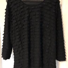 Farven er sort. Bluse med masser af stræk. Mærket er 'Bassini'. 3/4 ærmer. 92% polyester og 8% elastan. Brystvidde: 73 cm. X 2. Længde: 75 cm. Som ny.