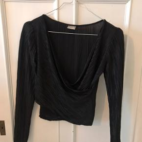 Flot sort bluse med crossover effekt og v-hals. Shiny i stoffet. Lille i størrelsen, så fitter også XS.
