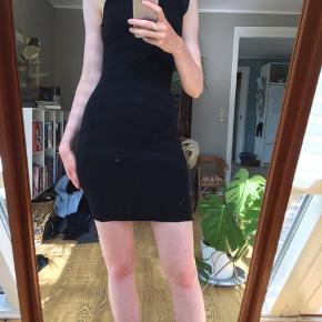 Fin sort kjole i elastisk stof. Dyb ryg med flæser i kanten