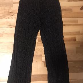 Sorte bukser med elastik i taljen, har et super fint glimmer stof som yderste lag.