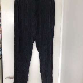 Fine Rosemunde bukser i 100% silke. Elastik i taljen og tyndt bindebånd. Bukserne er mønstrede mørkeblå og sort. Løst snit. Str 38.