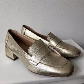 Loafers i guld-farve fra Wonders i den smukkeste kvalitet med metallisk look. Skoen er af læder og modellen er enkel med en firkantet snude og en hæl på 3 cm. Nemme og meget behagelige at have på og gode både til hverdag og til fest ✨  Skoene er helt nye.