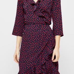 Populær slå-om kjole fra Vero Moda i blå med røde prikker. Størrelse L, men kan også sagtens passes af en størrelse M. Den sidder rigtig behageligt på kroppen. Kom med et bud :-) - jeg har også mulighed for at tage billeder af den rigtige kjole