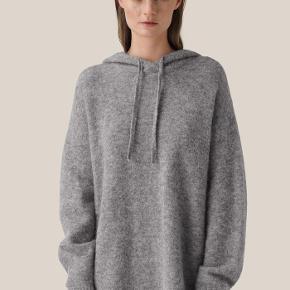 Denne hættetrøje i strik med løs pasform og ekstra længde er fremstillet i en blød alpaka- og uldblanding. Hætten har løbegang med strikket bindebånd.  32% Alpaka 32% Uld 30% Polyamide 6% Elasthan