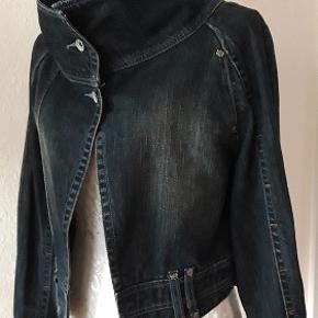 Kvalitet jeans jakke fra U by Uldahl. Kraftig god jeans kvalitet , farve mørke blå med original slitage look. Spændende facon, lukkes med 2 Uldahl  knapper. Små diskrete metal nitter med Uldahl kendemærke ., (se billeder)  Spændende krave . Oprindelig pris var 1900 . Aldrig brugt Længde   bag fra nakken -  47 cm Brystmål - 98 cm