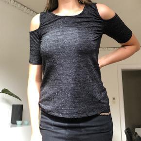 T-shirt med udskæringer i sort med sølvtråd.
